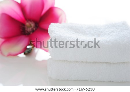 a stack of white towels with pink lily on white background