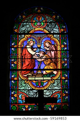 A stained glass window in a church depicting a scene from the Bible