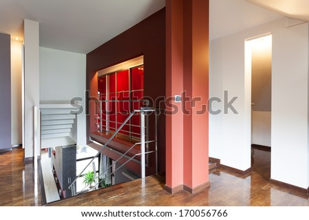 A stairway with a landing with a modern red wall