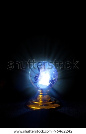 A stand alone crystal ball, glowing with rays shooting forth and strange patterns within. - stock photo