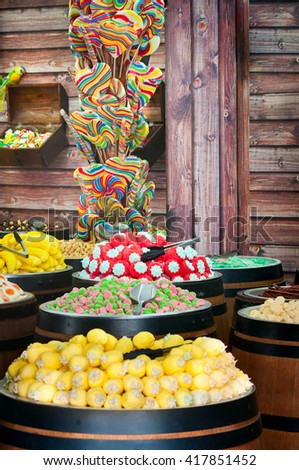 A stand with wide assortment of multicolored candy on a wooden background - stock photo