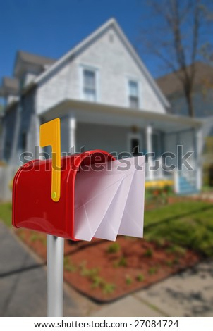 A standard red mailbox american money and flag in front of a house - stock photo