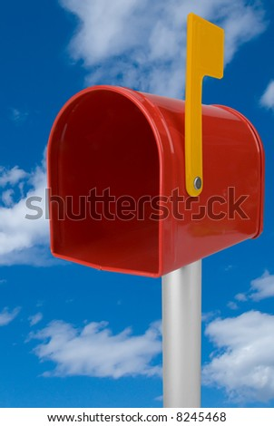 A standard red mailbox and flag isolated over a blue sky - stock photo