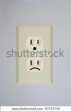 A standard wall electrical outlet contains two surprised faces. This one has one replaced by a sad face.