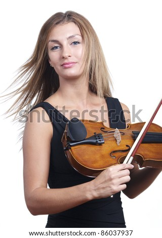 A standing woman dressed for the symphony finishes playing her violin - stock photo