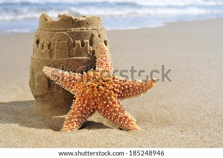 a starfish and a sandcastle on the sand of a beach - stock photo