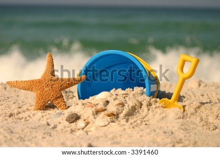 A starfish and plastic bucket at the beach - stock photo