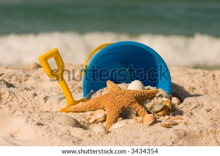 A starfish, shells, and and beach toys set against the crashing surf.  Shot with shallow DOF. - stock photo