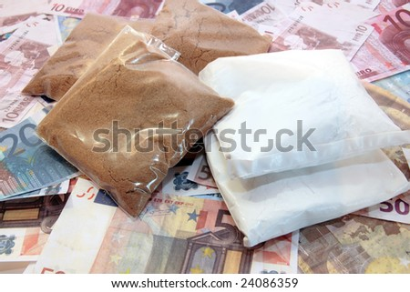a stash of drugs and money showing a high cost to life - stock photo