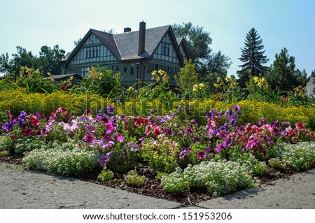 A stately home with large flower garden. - stock photo