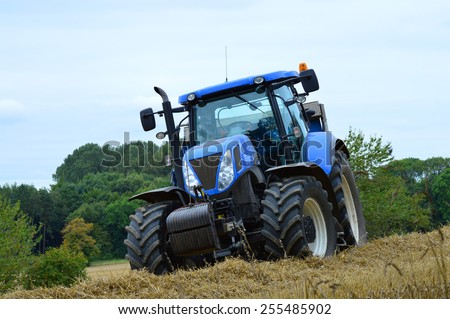 A stationary blue tractor is parked on the edge of a field of barley against an overcast sky.