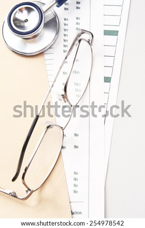 A statoscope and glasses on papers from above - stock photo
