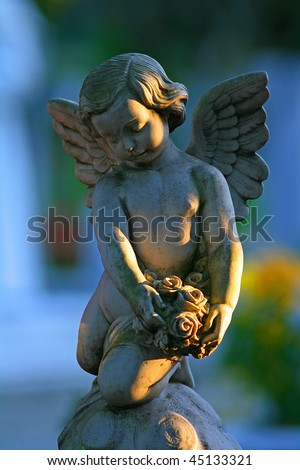 A statue of a baby angel in a Christian cemetery - stock photo
