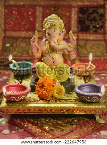 A statue of a mythological elephant god -Ganesha, surrounded by traditional divali lamps - stock photo