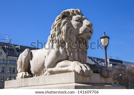 A statue of a reclining lion in the center of Oslo near the parliament - stock photo