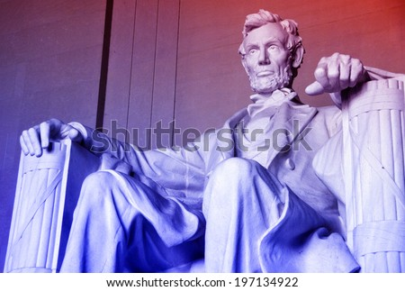 A statue of an old man sitting on a chair. - stock photo