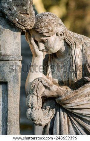 a statue of crying woman on the graveyard - stock photo