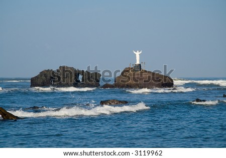 A statue of Jesus stands on a small island of volcanic rocks - stock photo