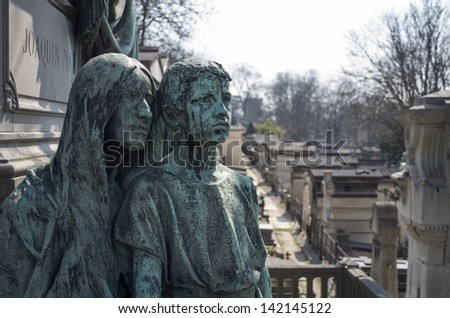 A statue or sculpture on a grave site at Pere Lachaise Cemetery in Paris, France. - stock photo