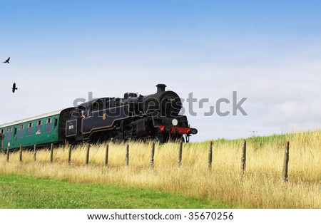 A steam engine pulling a passenger carriage on the track along the Swanage railway network. Location in Dorset UK. - stock photo