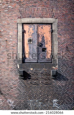A steel door on the side of a waterfront warehouse which allows access to docked ships. - stock photo