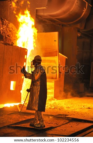 A steel worker takes a sample from oven - stock photo