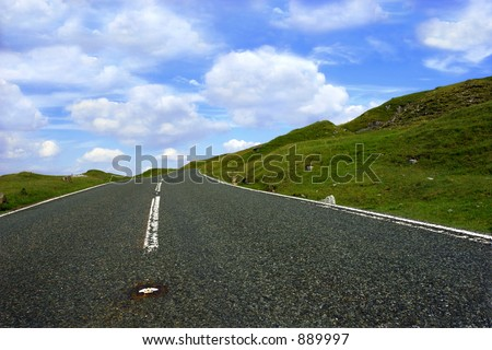 A steep uphill road with grass verges on either side with a blue sky and clouds. Set in the Brecon Beacons National Park, Wales UK - stock photo
