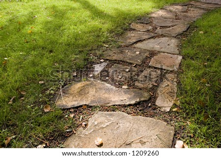A stepping-stone pathway surrounded by green grass - stock photo
