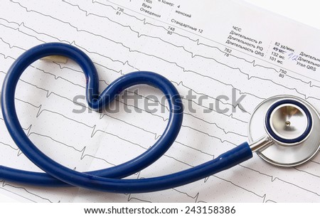 A stethoscope in a shape of heart lying on a cardiogram - stock photo