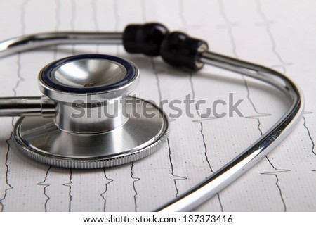 A stethoscope on a cardiogram - stock photo