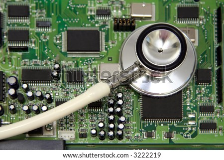 A stethoscope on a computer circuit board. Possible concept uses: computer health,  technology in healthcare, diagnosing/troubleshooting PC problems, medical technology. - stock photo