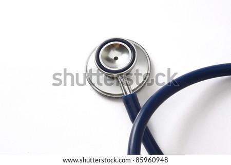 A stethoscope on white, closeup - stock photo