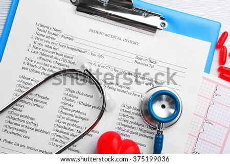 A stethoscope, pills, plastic heart and clipboard, close-up - stock photo