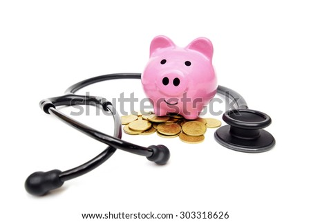 a stethoscope with pink piggy bank and golden coins - saving money for healthcare concept - stock photo