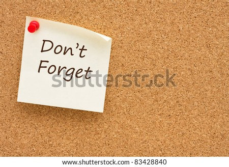 A sticky note on a cork board with the words do not forget on it - stock photo