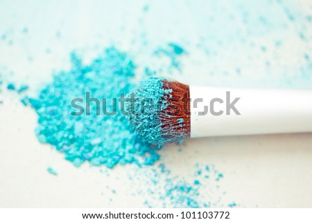 a still-life of colourful eyeshadow powder and make-up brush