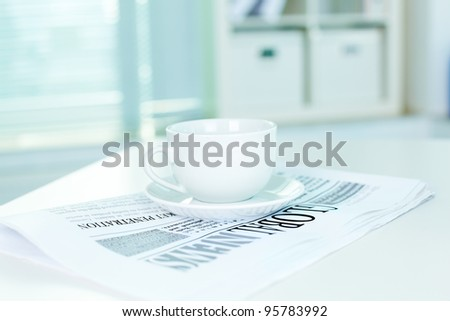 A still of white cup standing on a fresh newspaper in office - stock photo