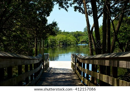 A still river showing reflections is seen at the end of a pier or boat dock at the end of a boardwalk in Bonita Springs Florida. - stock photo