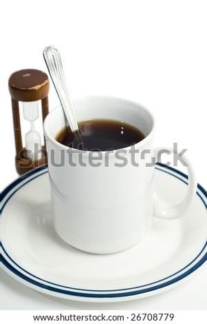 A stirred cup of coffee and an hourglass, shot against a white background - stock photo