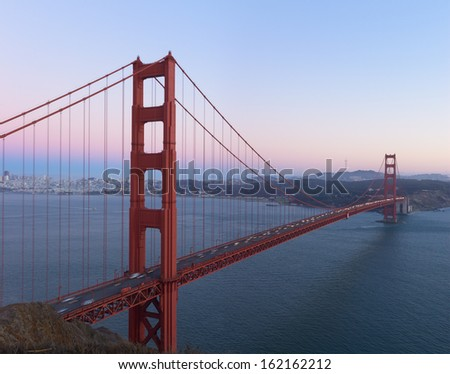 A stitched image of Golden Gate Bridge at Sunset shot from Battery Spencer. Delicate pink hues in the sky, San Francisco in the background.