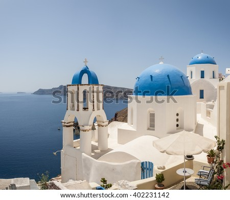 A stitched panorama of a couple of the famous blue domed churches from Oia on the greek isle of Santorini.