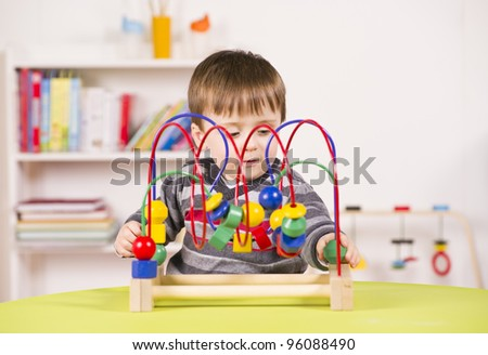 A stock photo of a child playing with a challenging toy in the play room - stock photo