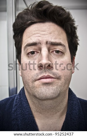 A stock photo of a man who is looking in the mirror after a big night out