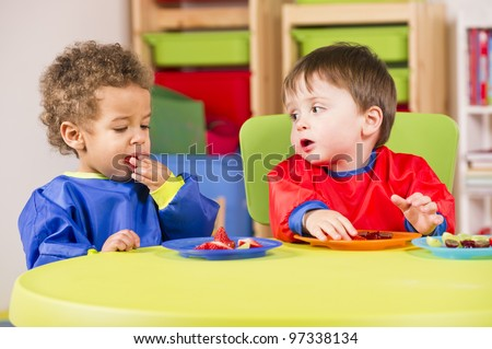 A stock photo of toddlers eating fruit and having a chat in the playroom - stock photo