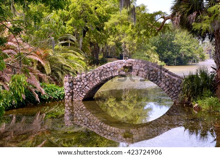 A stone bridge over a quiet lagoon, with reflections in water. - stock photo