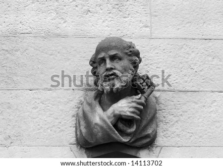 A stone carving of Saint Peter above the main door on the outside of the Chapel Royal in Dublin. He is holding the traditional symbols of cross and key. (In black and white.)