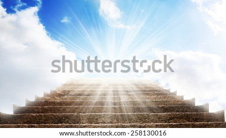 A stone stair in the way up to blue sky, there is a strong light in the end of the way