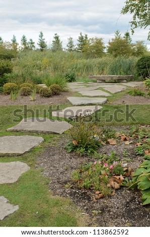 a stone walkway leads to a stone park bench overlooking a small pond - stock photo