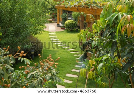 A stone walkway winding its way through a tranquil garden - stock photo