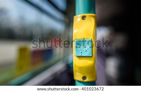 A stop button on a public bus with additional braille.
